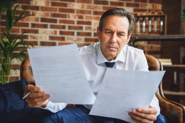 Exhausted mature businessman is sitting in room. He holding documents and reading it