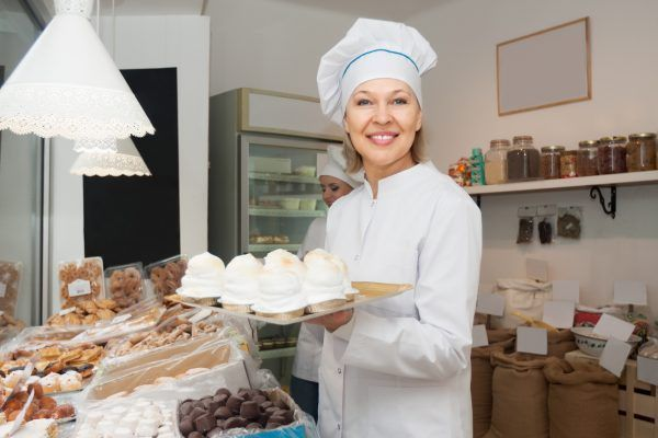 Portrait of friendly mature woman at confectionery display with pastry