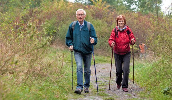 Senior couple Nordic walking on rocky trail in the nature.